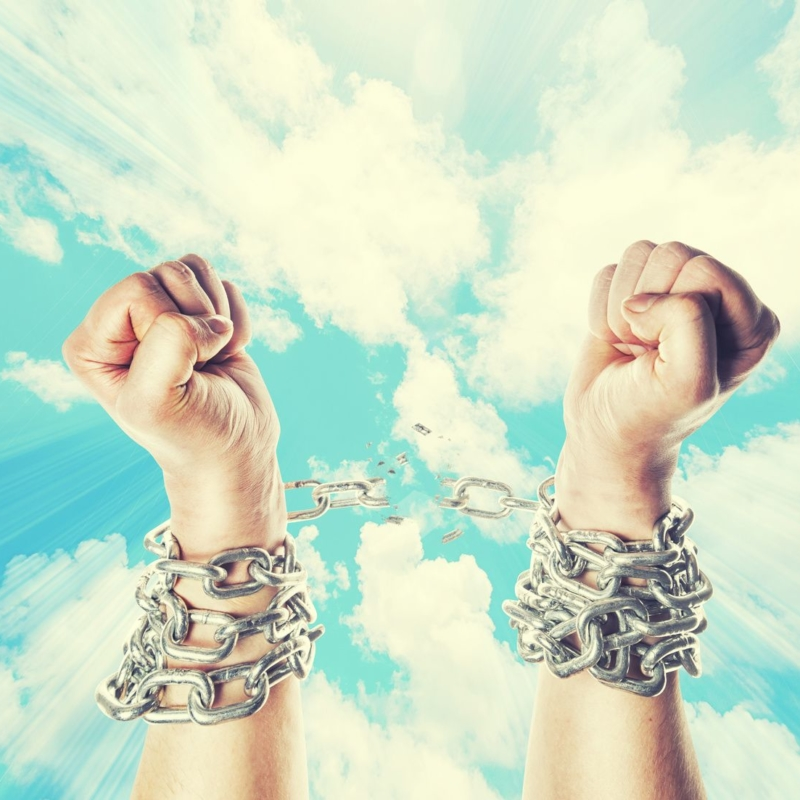 Two hands in chains on a heavens background with a flash